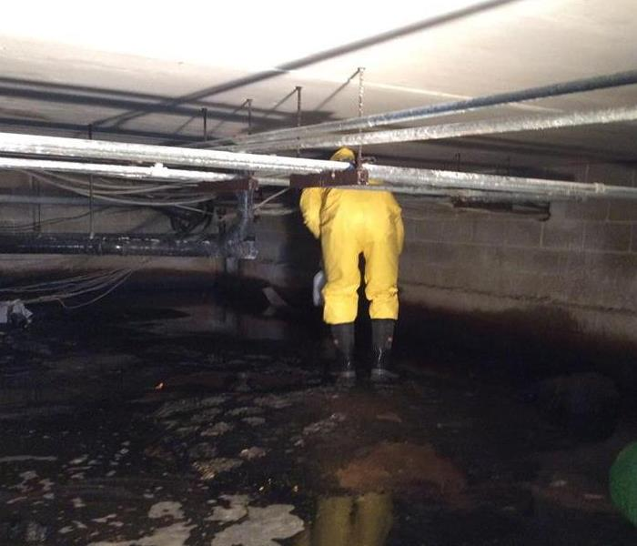 water flooded in crawlspace being extracted by worker