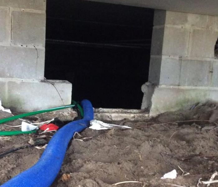 A home crawlspace with dust and debris present. A water extractor is in place.