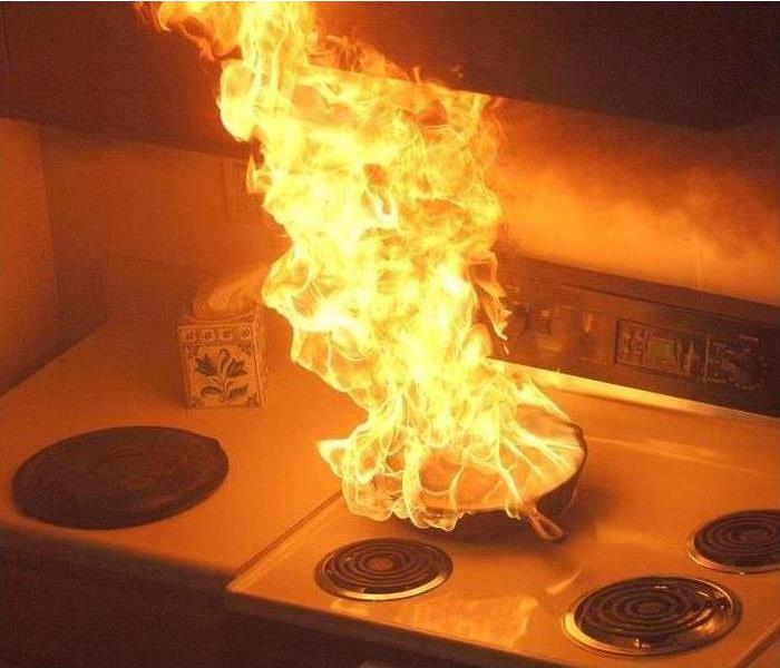 Flames in a frying pan on a kitchen stove
